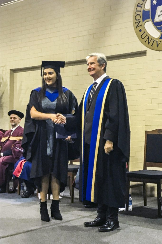 Catenian Scholarship recipient Ashleigh Habkouk and UNDA Chancellor Christopher Ellison pose for photographers at Ms Habkouk's graduation ceremony, where she delivered the valedictory speech. Photo: Supplied.