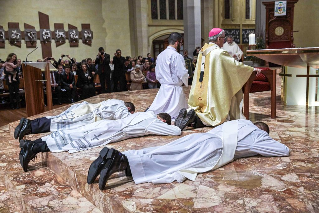 Father's Liam Ryan, Mark Rucci and Matteo Verdi prostrate during their Ordination Mass on Friday 16 August at the St Mary's Cathedral. Photo: Ron Tan.