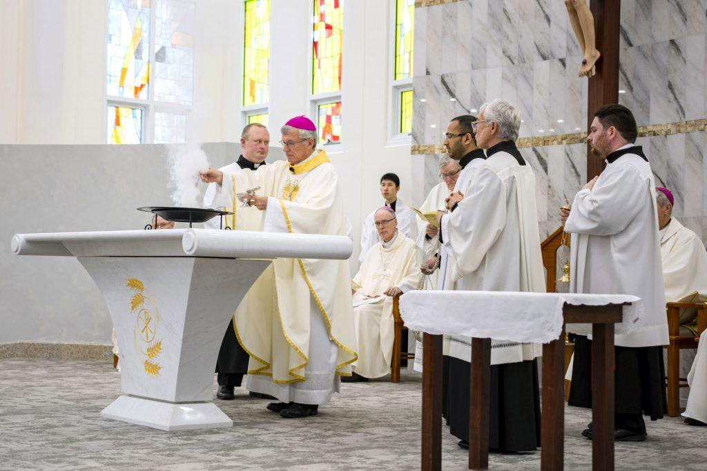 Archbishop Timothy Costelloe lights the incense to be used during the ceremony from a specially prepared brazier. Photo: Eric Martin.