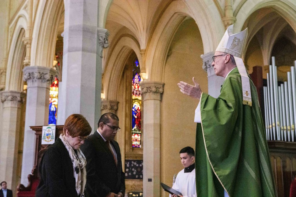 Bishop Sproxton imparts a blessing onto the two new directors of Flame. Photo: Amanda Murthy.
