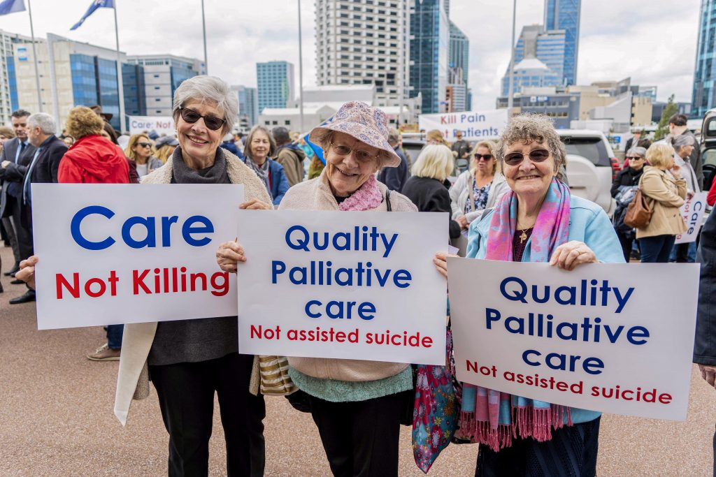 Peaceful protestors hold placards showing their support for palliative care as the preferred treatment option for the elderly. Photo: Josh Low.