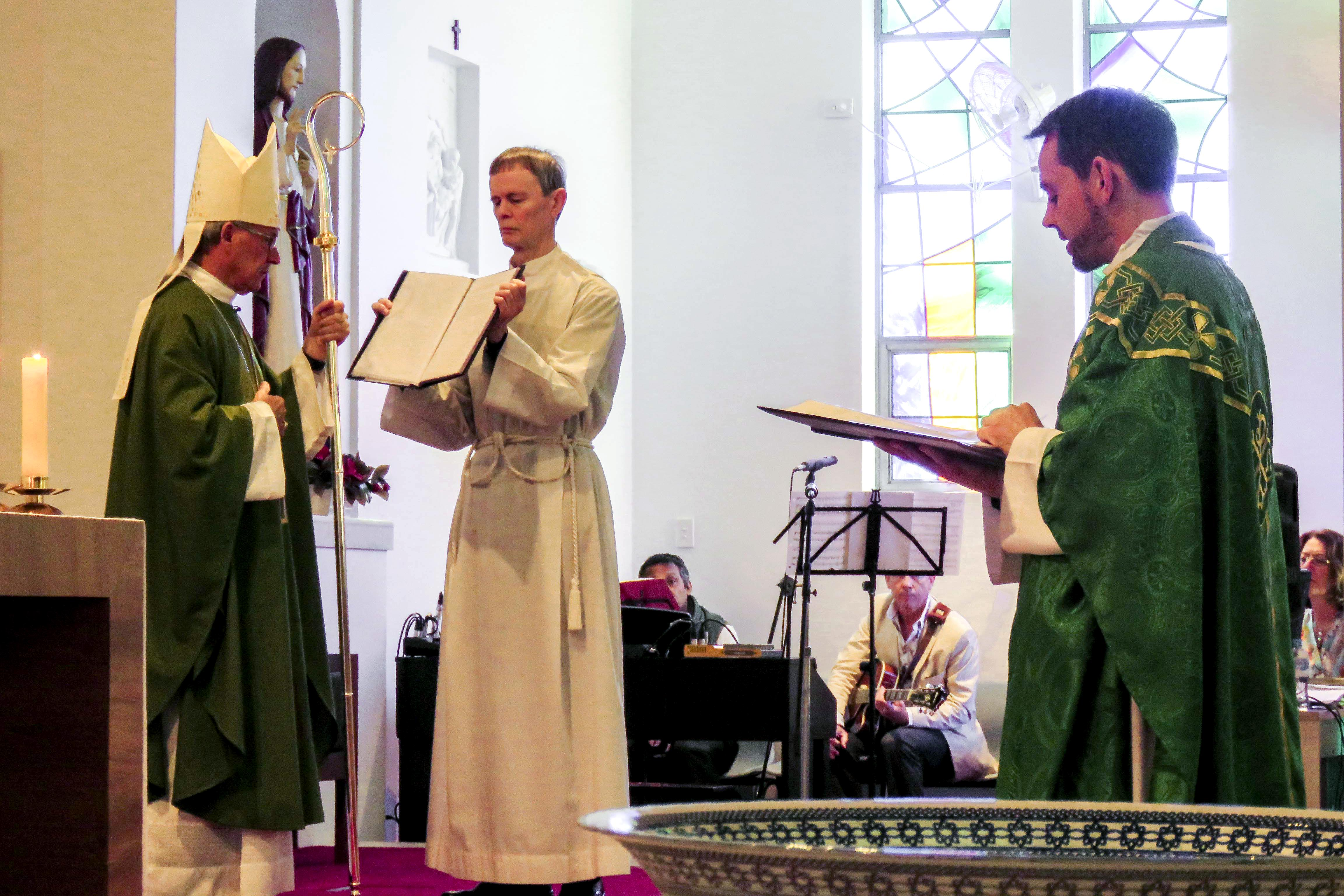 Fr Gorddard makes his Profession of Faith and Oath before the Archbishop as part of the Rite of Installation of a Parish Priest. Photo: Bridget Curran.