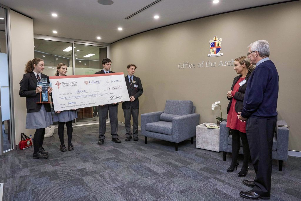 Students from Prendiville Catholic College present Archbishop Costelloe with a copy of the cheque. Photo: Ron Tan.