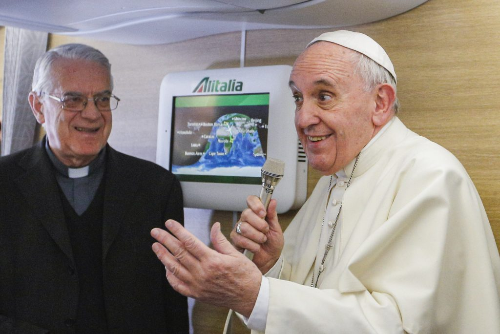Jesuit Father Federico Lombardi, looks on as Pope Francis talks to journalists in 2015 aboard his flight from Rome to Nairobi, Kenya. The retired papal spokesman says Pope Francis' communications style differs from Pope Benedict's but both papacies reflect continuity based on pontiffs' understanding of the church. Photo: CNS/Paul Haring.