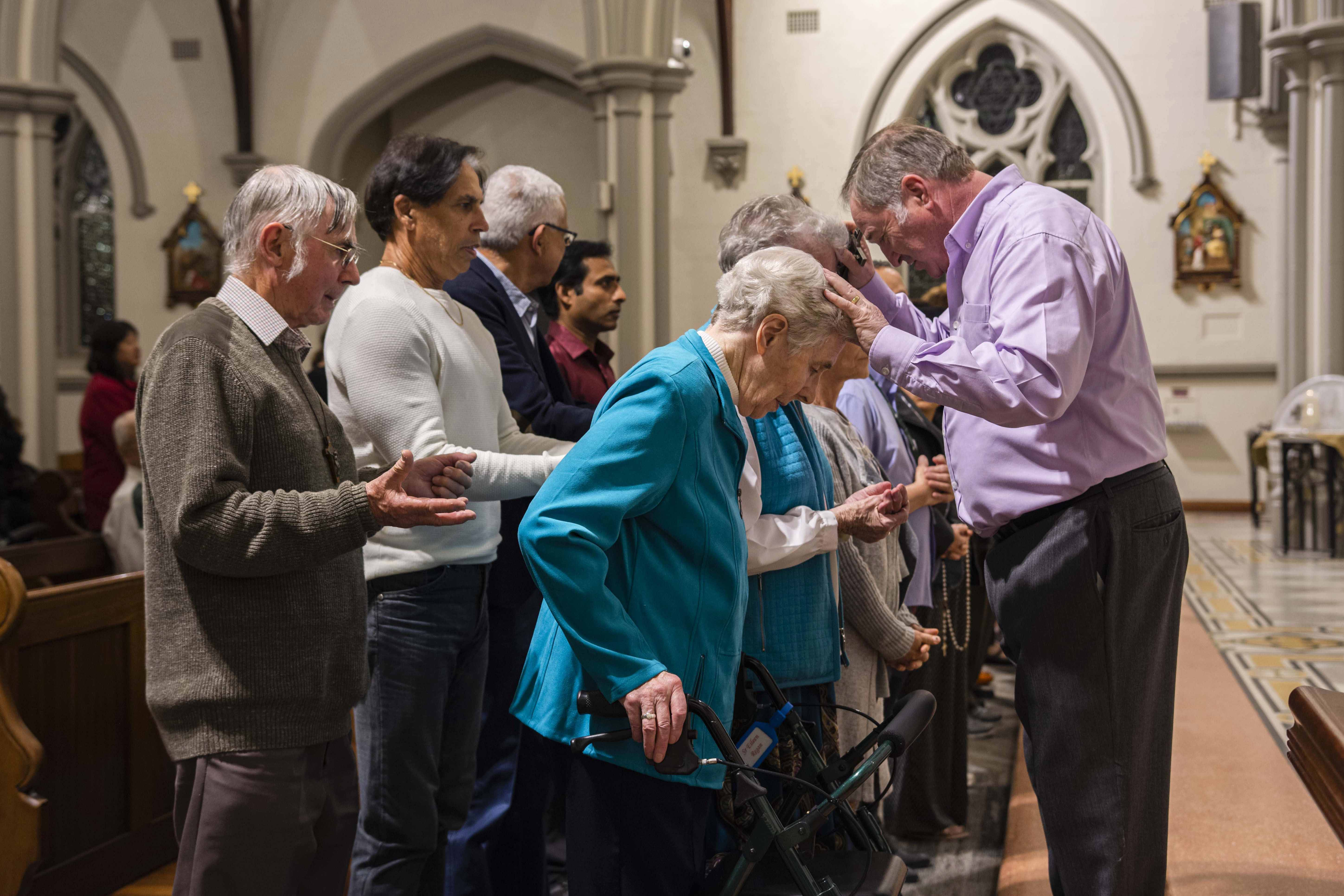Parishioners of St Joseph's Subiaco gather to have Alan lay hands on them in prayer for healing. Photo: Eric Martin.