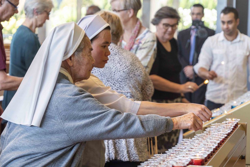 Religious Sisters light a candle as part of the Interfaith Prayer Service. Photo: Josh Low.