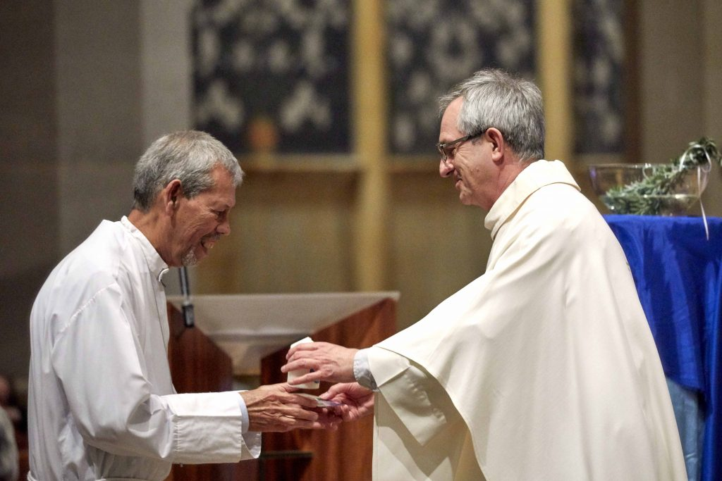 SVDP Chaplain Fr Nino Vinciguerra presents a memorial candle to one of the Society's Regional Presidents. Photo: Ron Tan.