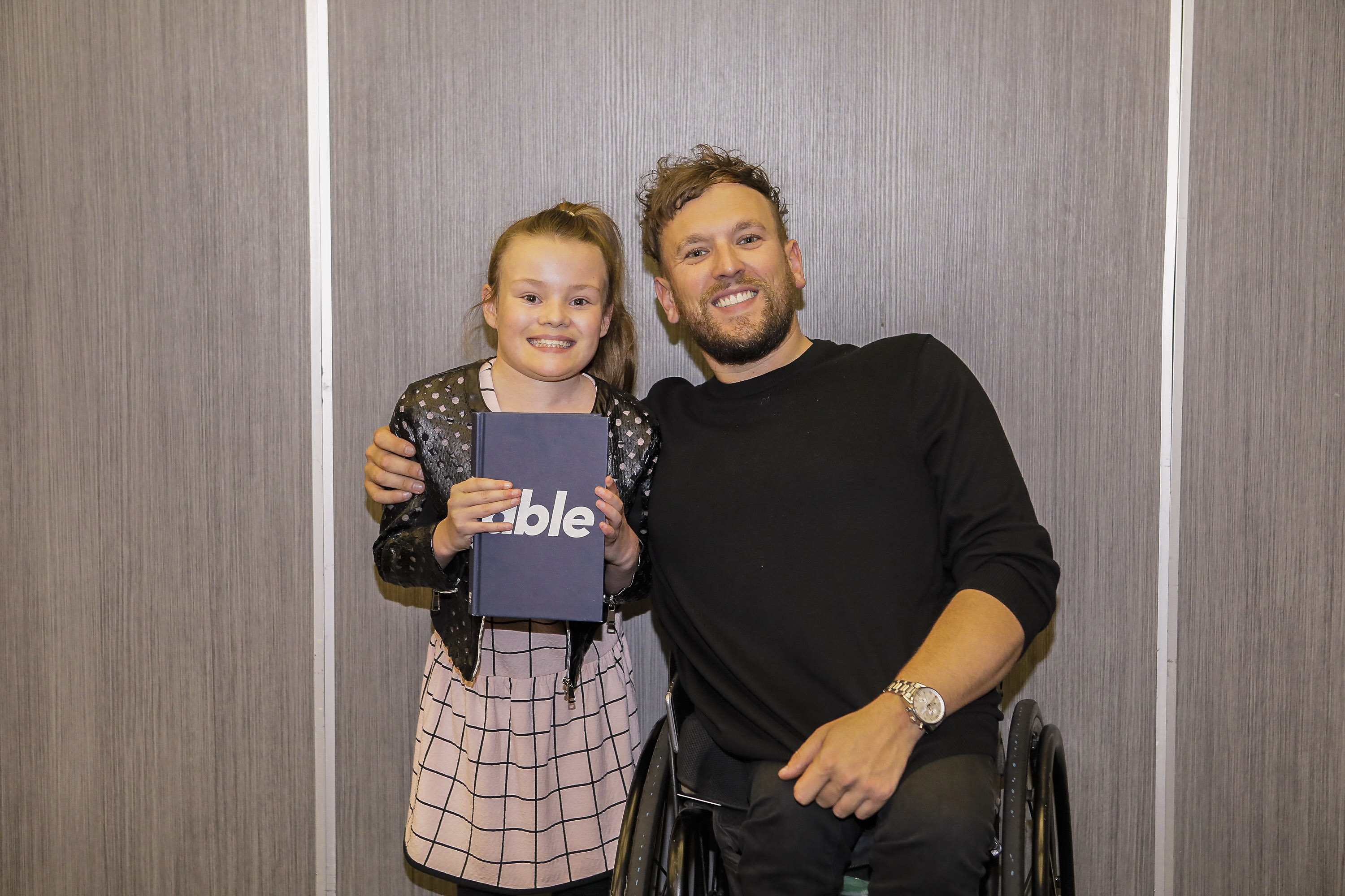 Guest Madi with Dylan Alcott OAM at the MercyCare Oration 2019 at the Perth Convention and Exhibition Centre on September 23. Madi is holding Dylan's book titled Able. Photo: MercyCare.